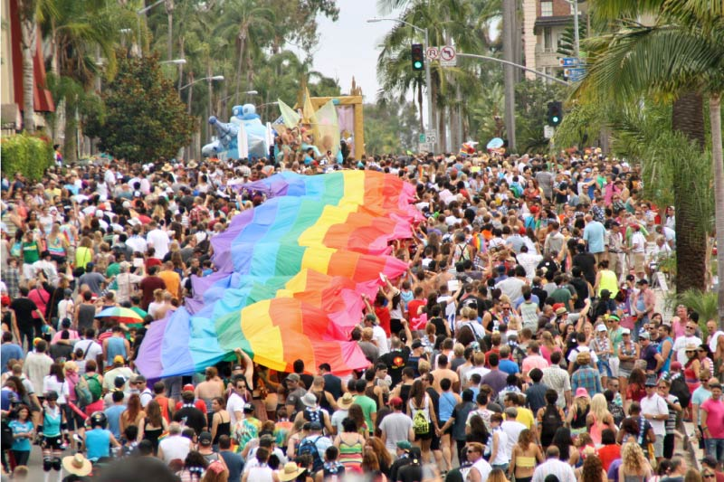Participants of the San Diego Pride parade carry a LGBTQ pride flag down the street.