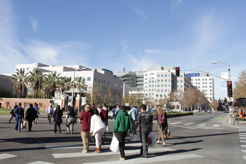 People crossing the intersection of Westwood Plaza and Le Conte Ave on the UCLA campus.