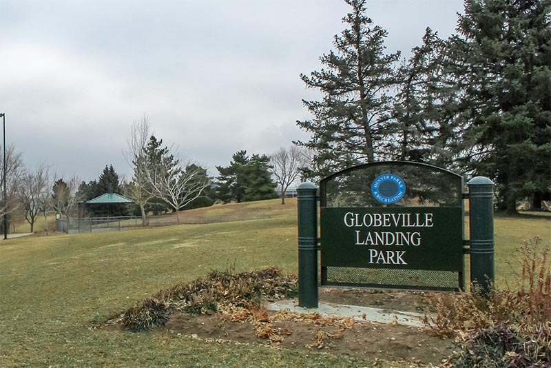 A park entrance sign for Globeville Landing Park sits on a grassy hill in Denver