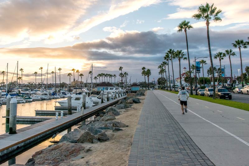 A person running along the path adjacent to the Long Beach Marina.