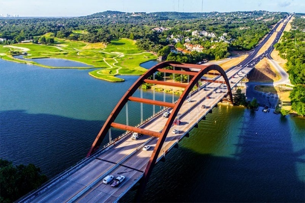 An aerial view of the Pennybacker Bridge in Austin with cars driving along either side of the roadway over a river