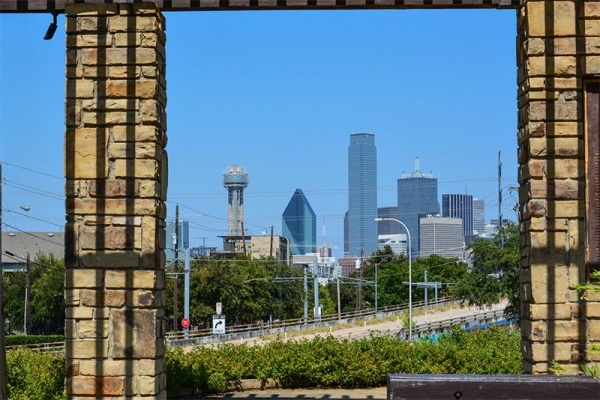 Dallas skyline seen from far away behind two pillars