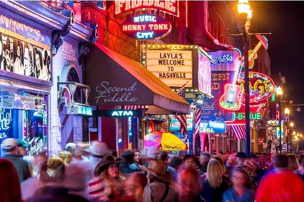 Crowds of people walk by neon signs and storefronts lining the lower broadway area of Nashville