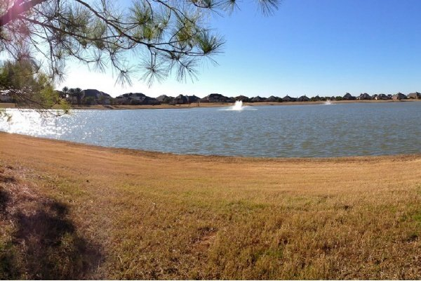 Panorama photo looking west over a body of water from the path behind a home in Cypress Texas.