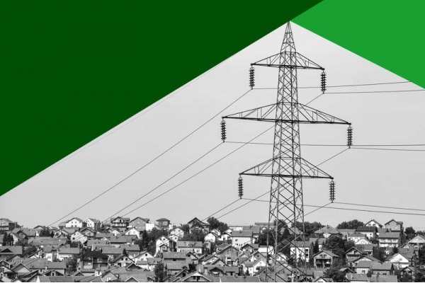 A black and white photo of large power line rises above a hill of small homes with green triangles above