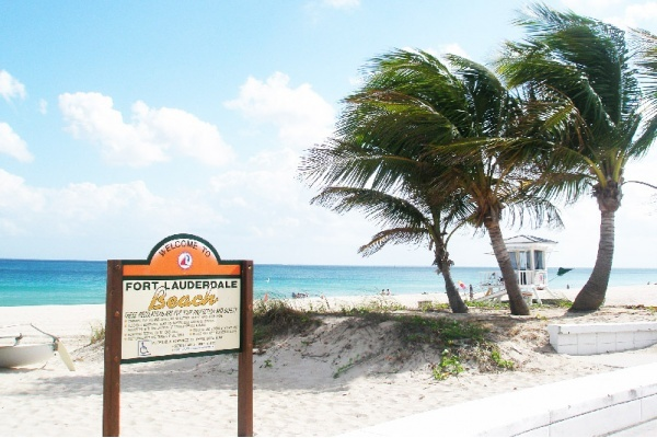 Fort Lauderdale Beach sign in front of the beach and trees.