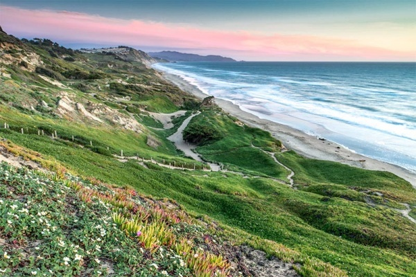 A trail snaking down a large cliff to a beach with the ocean crashing in with pink skies in San Francisco