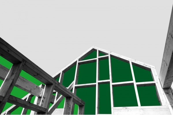 A wood frame of a house being built in black and white, with green shapes behind it