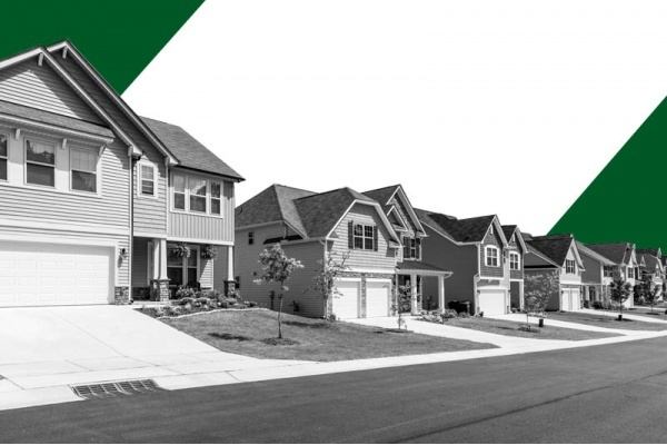 A street of residential suburban homes in black and white with green triangles behind it