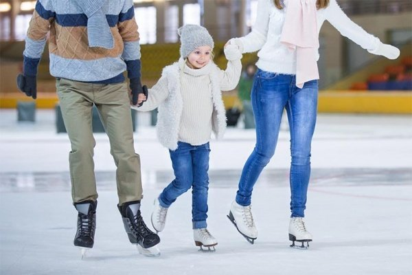 An image centered low on three people ice skating at an ice rink