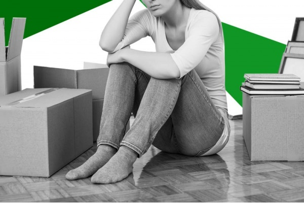 A woman surrounded by filled boxes with her hand on her head looking stressed