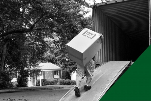 A black and white image with a green triangle that shows a man moving a large box into a moving truck