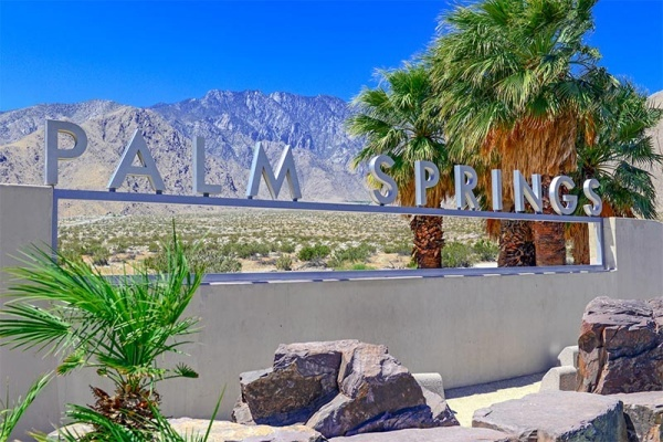 A metal sign that says Palm Springs in front of a backdrop of mountains and palm trees