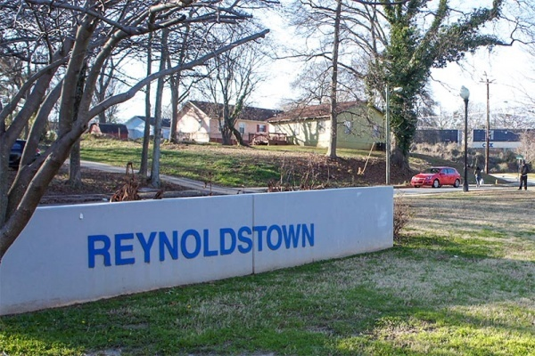 A small wall in the center of a grassy park that says Reynoldstown in Atlanta