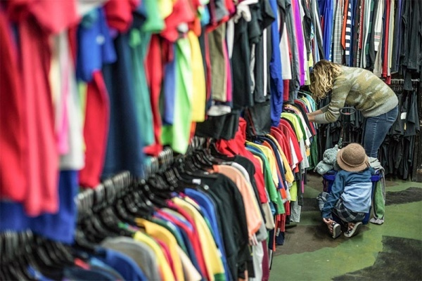 A woman and a child looking through clothing racks at a thrift shop
