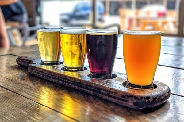 A flight of different colored beers on a wooden table in Indianapolis