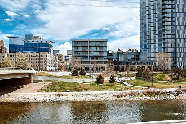 A view from across a river of apartments and condominiums along a park in Denver CO