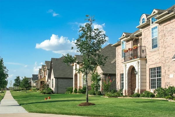 A residential street of luxury homes in Texas with large front lawns against a blue sky