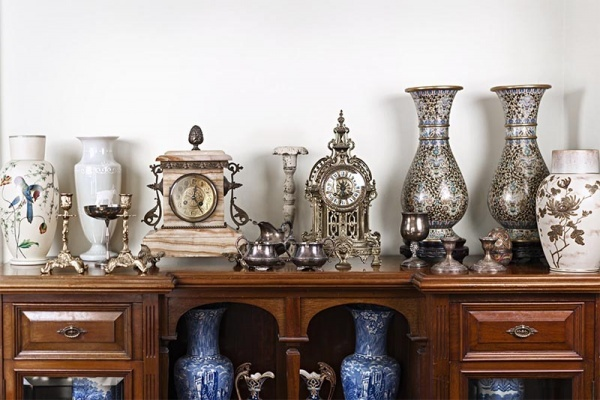 Antique vases, clocks, and candle holders sit on a wood table
