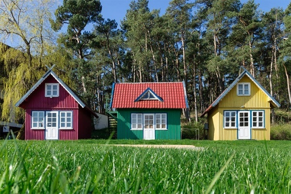 A row of three tiny houses, one red, one green, and one yellow in front of a stand of trees