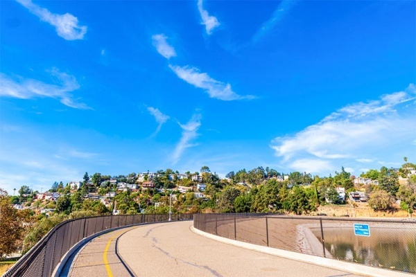 The Silver Lake Reservoir Trail with houses on hills in the background in Los Angeles
