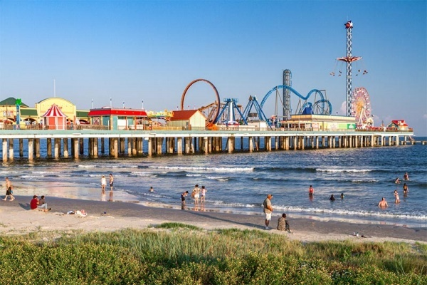 People at the beach next to the famous Pleasure Pier in Galveston Texas