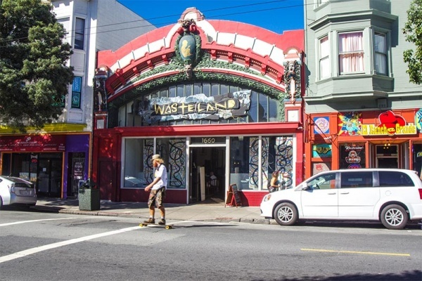 The facade of a red ornate thrift store front that says Wasteland with green accents in San Francisco