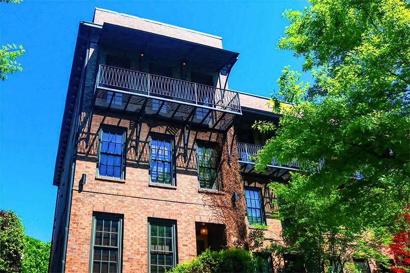 An upward view of a brick condominium building with a balcony against a blue sky