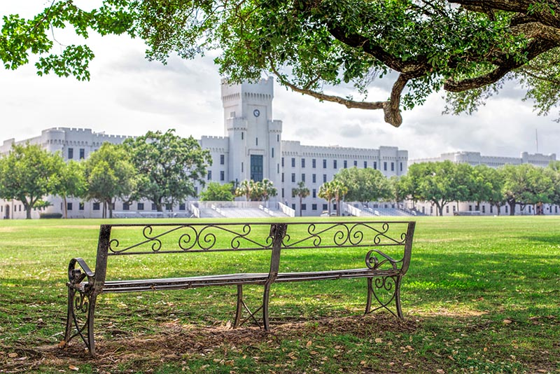 A bench sits in a grassy park in front of the famous Citadel in Charleston