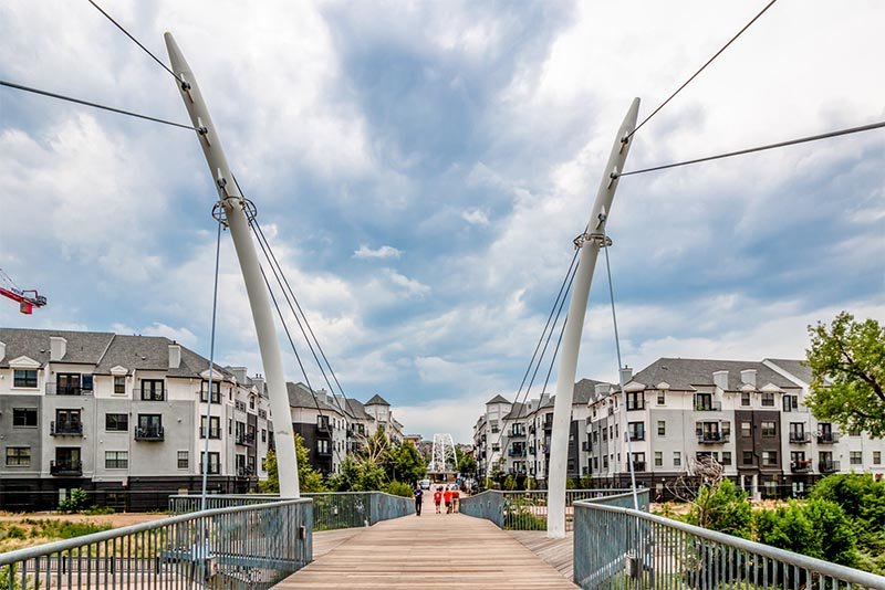 A suspended foot bridge crosses to a residential area in Denver Colorado