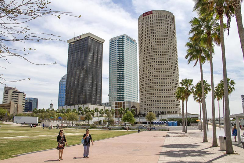 People walking in park with high rise buildings in background.