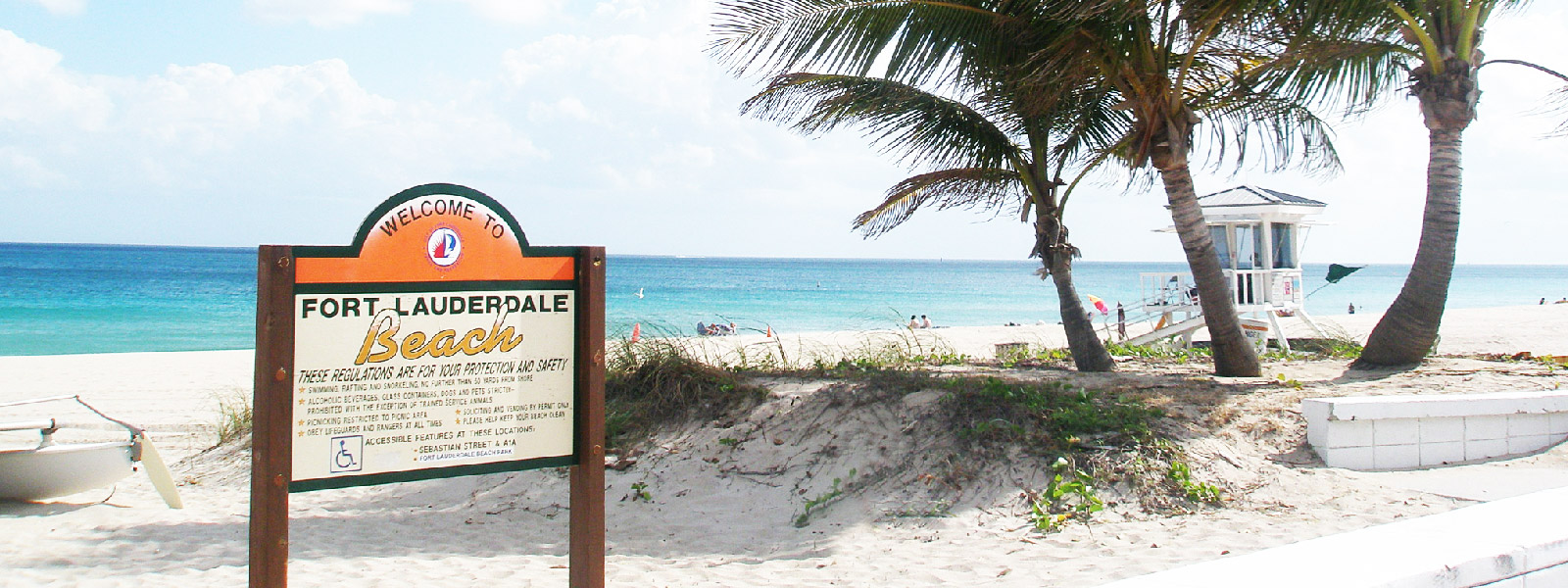 Fort Lauderdale Beach sign in front of the ocean and palm trees.
