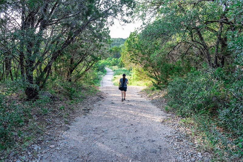 A hiker walks down the middle of a trail in Government Canyon State Park