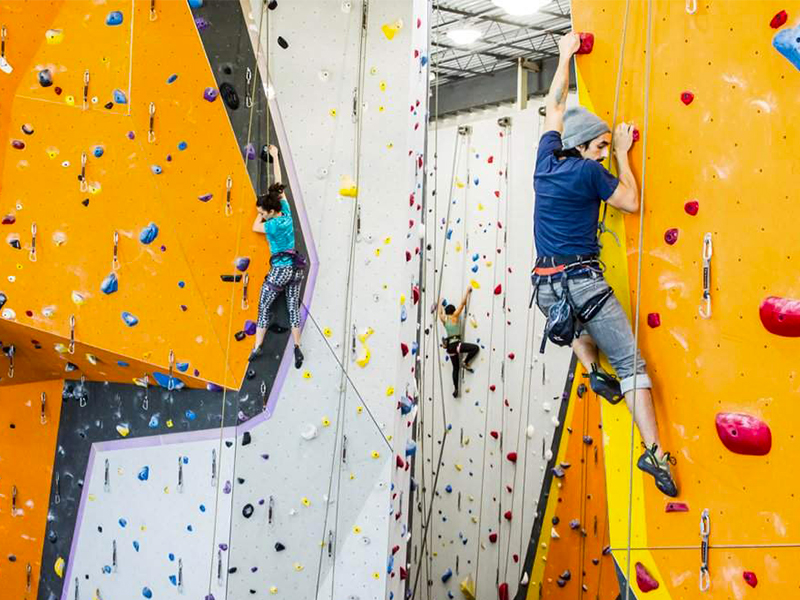 Person climbing indoor colorful rock climbing wall at First Ascent in Chicago.