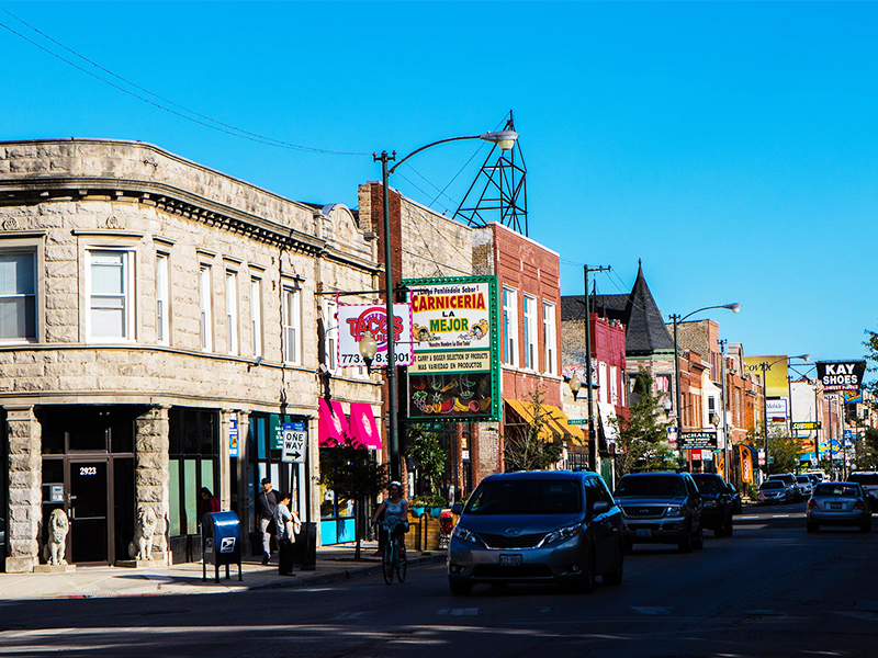 Street scene with line of restaurants and colorful signs in Chicago's Avondale neighborhood.