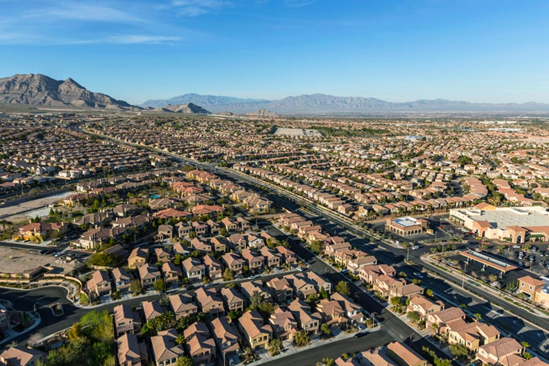 Aerial of homes and neighborhoods in suburban las vegas and mountains in distance.