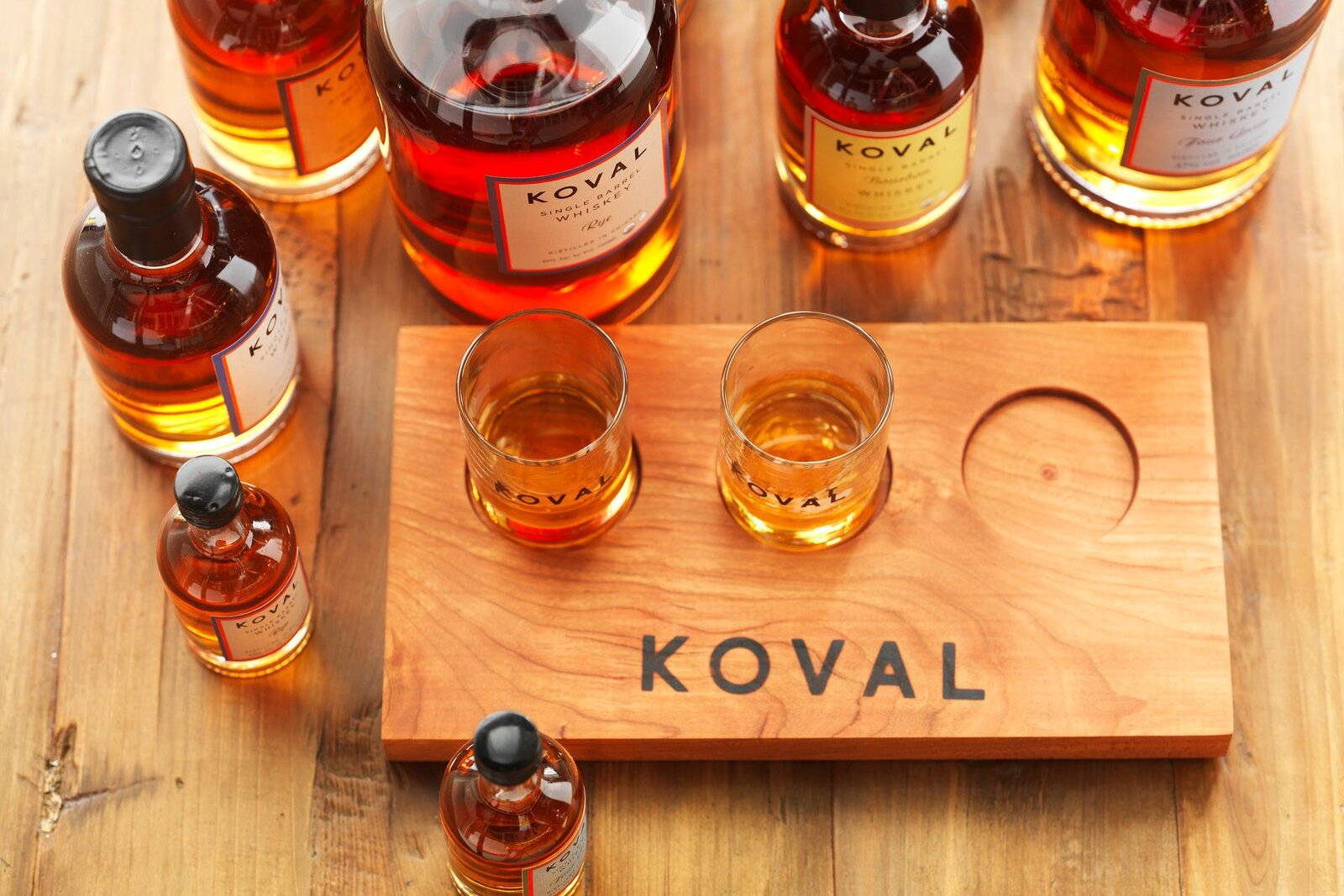 Looking down at several different glasses of whiskey on a Koval whiskey tasting board.