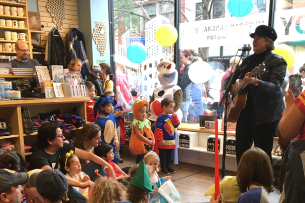 Women singing to group of kids dressed up for Halloween.