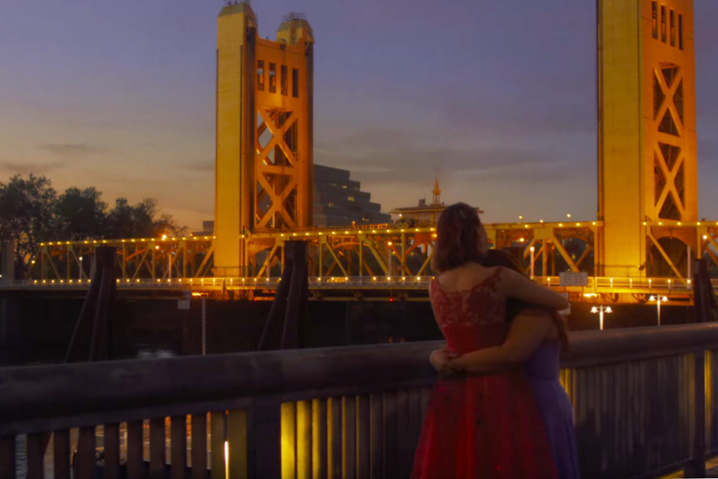 Two girls hug along river in front of Sacramento Tower Bridge at sunset.