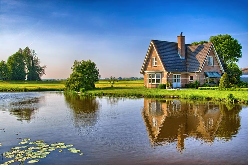 Brick home along pond in open field