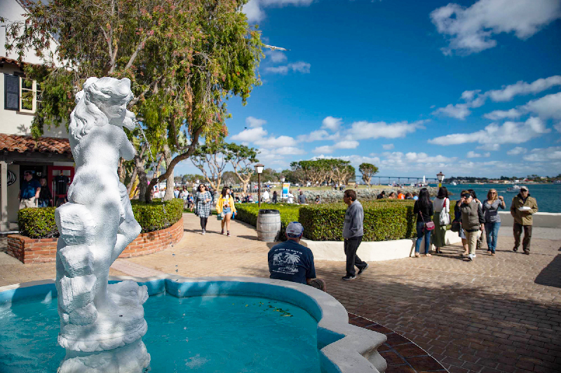 People walking along San Diego's marina district with closup of fountain and statue.