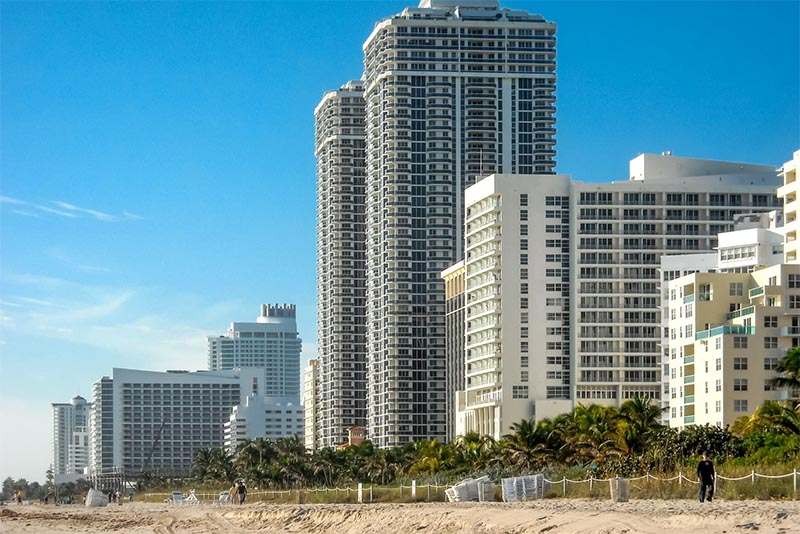 Condominium buildings on the right rise up above palm trees and the beach in Mid-Beach Miami Florida