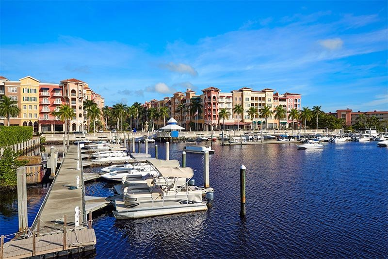 A view of condominium buildings rising up from docked boats below in Naples Florida