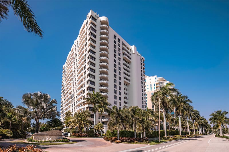 A large condominium building on a palm-tree lined street in Park Shore Naples Florida