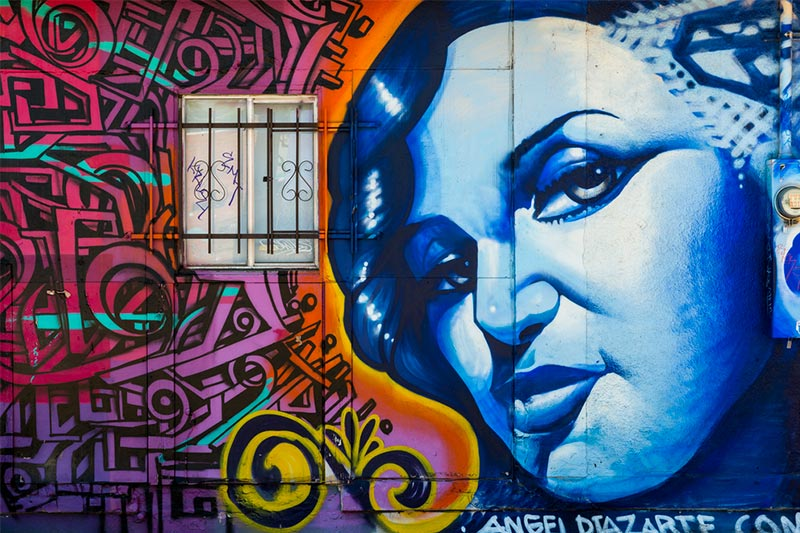 Bright and vibrant mural on side of young woman on side of building in Roosevelt Row, AZ.