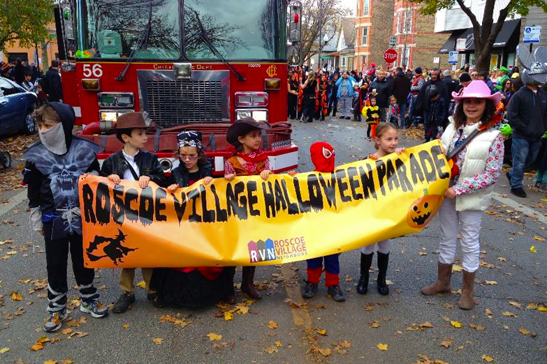 Dressed up children holding sign for Roscoe Village NEighbors Halloween Parade and Party.