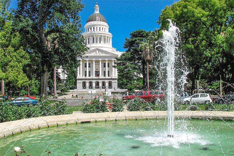 A view of the California Capitol building in Sacramento from near a fountain in front of it