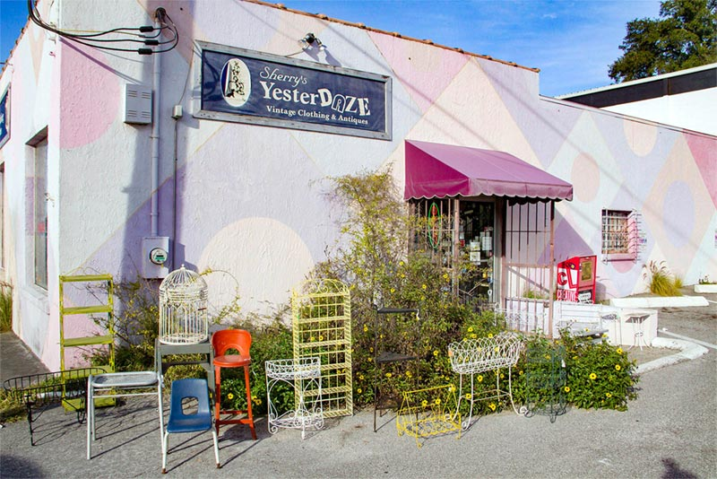 Pink neighborhood shop with various chairs out front.