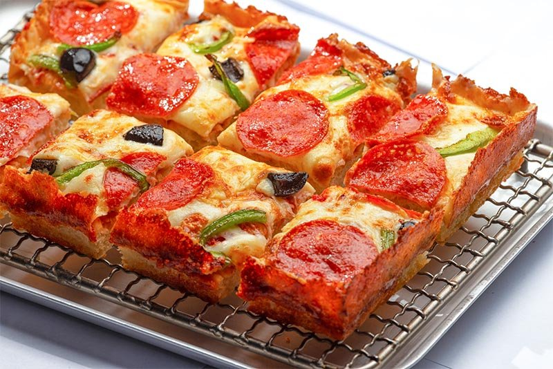 A sliced Detroit-style pizza sitting on a cooling tray