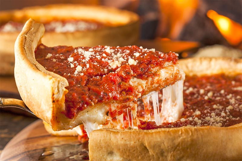 A slice of Chicago deep dish pizza being pulled from the pan